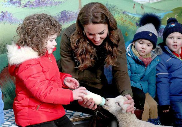 PHOTO: Britain's Catherine, Duchess of Cambridge reacts as helps children bottle-feed a lamb during her visit to Ark Open Farm near Belfast on Feb. 12, 2020. (Liam Mcburney/AFP via Getty Images)