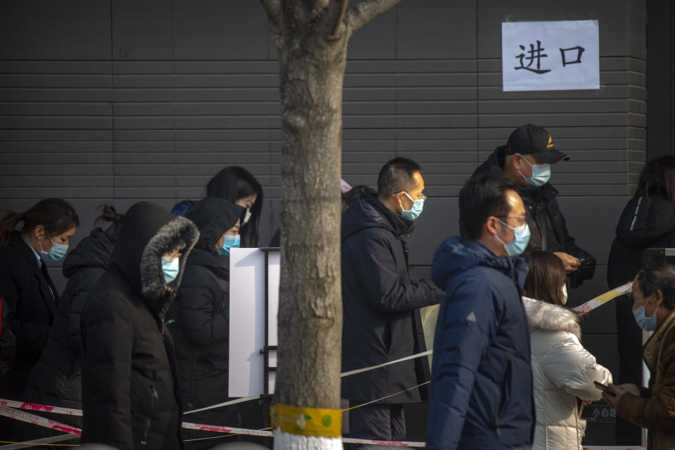 People wearing face masks to protect against the spread of the coronavirus prepare to enter a site for mass COVID-19 testing in a central district of Beijing, Friday, Jan. 22, 2021. Beijing has ordered fresh rounds of coronavirus testing for about 2 million people in the downtown area following new cases in the Chinese capital. (AP Photo/Mark Schiefelbein)