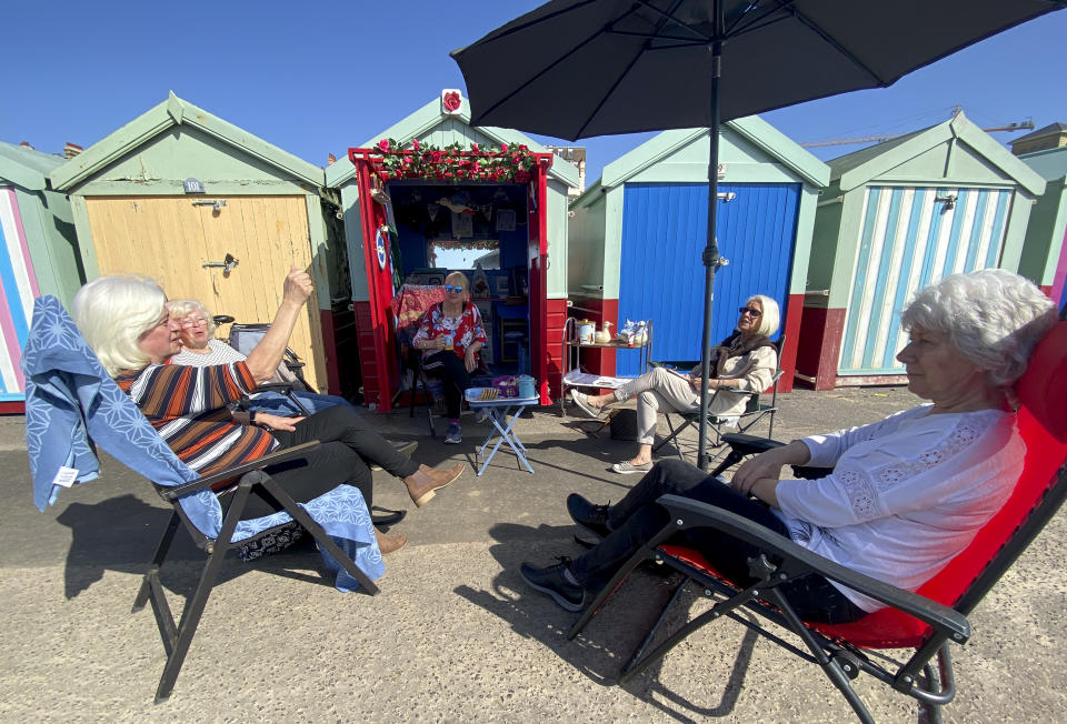 BRIGHTON, ENGLAND - MARCH 30: Members of the University of the Third Age iPhone photography group take advantage of the easing of lockdown and unseasonably warm weather to have an impromptu get together at Roses beach hut at Hove Lawns on March 30, 2021 in Brighton, England. Parts of the UK are set to see the warmest day of the year so far as forecasters are predicting temperatures of 22C (72F). With the easing of pandemic lockdown rules, many people will be heading for the outdoors. (Photo by Chris Eades/Getty Images)