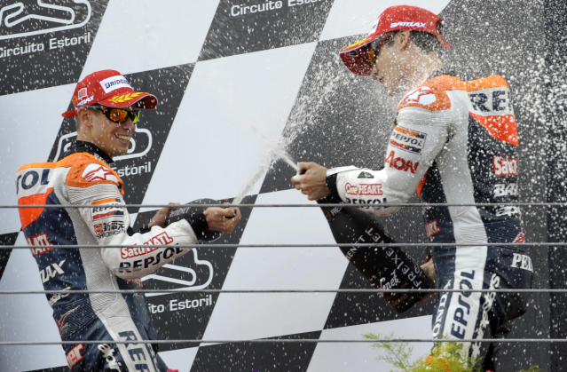 Repsol Honda team's Australian Casey Stoner (L) sprays cava over his teammate Spain's Dani Pedrosa on the podium after winning the Moto GP race of the Portuguese Grand Prix in Estoril, outskirts of Lisbon, on May 6, 2012. Stoner won the race ahead Spanish Jorge Lorenzo and Dani Pedrosa. AFP PHOTO / MIGUEL RIOPAMIGUEL RIOPA/AFP/GettyImages