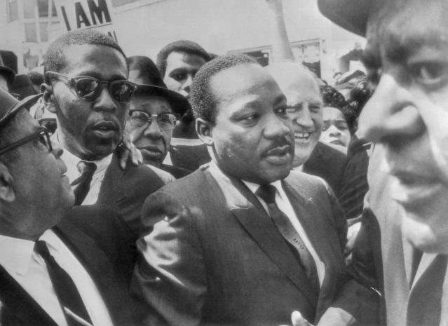Dr. Martin Luther King (center) is surrounded by leaders of the sanitation strike here as he arrived to lead a march in support of the striking workers on March 28, 1968. Shortly after the march began, bloody violence and looting began, forcing the National Guard to be called in. (Bettmann/Getty Images)