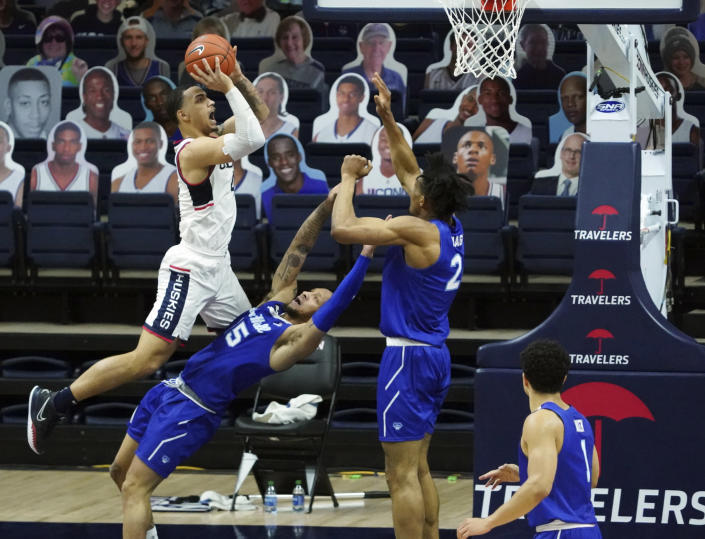 Connecticut guard Tyrese Martin (4) fouls Seton Hall guard Takal Molson (15) during the second half of an NCAA college basketball game, Saturday, Feb. 6, 2021, at Harry A. Gampel Pavilion in Storrs, Conn. (David Butler II/Pool Photo via AP)
