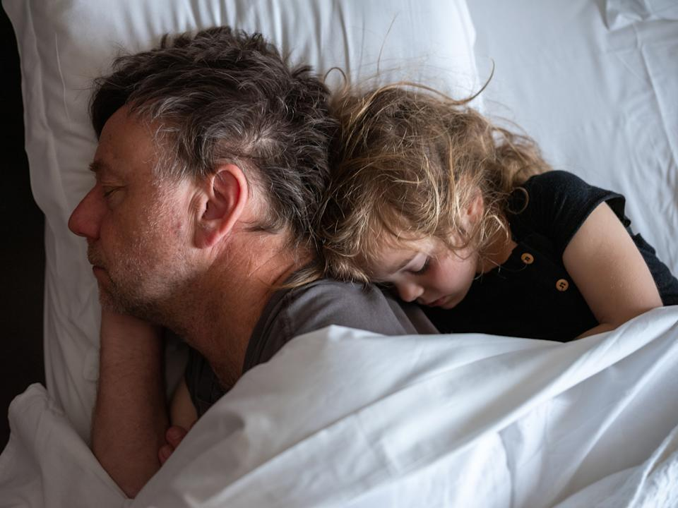 Father and daughter cuddling in bed
