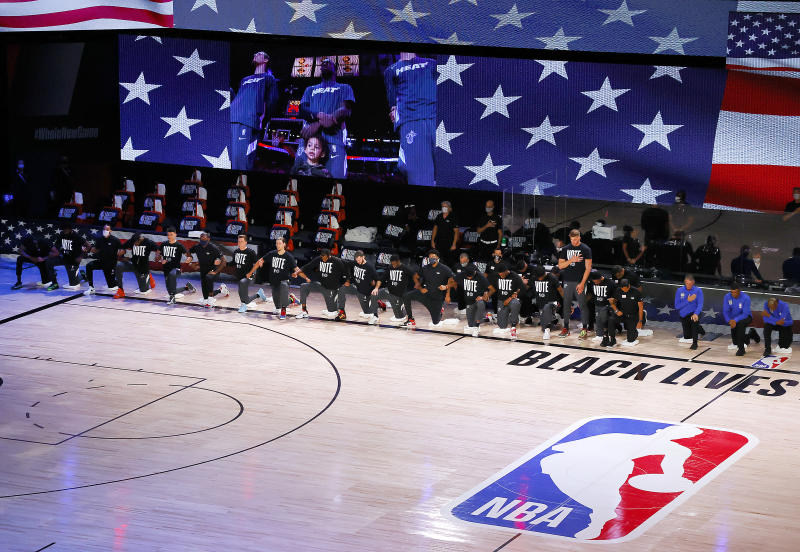 LAKE BUENA VISTA, FLORIDA - SEPTEMBER 23: The Miami Heat kneel during the National Anthem prior to the start of the game against Boston Celtics in Game Four of the Eastern Conference Finals during the 2020 NBA Playoffs at AdventHealth Arena at the ESPN Wide World Of Sports Complex on September 23, 2020 in Lake Buena Vista, Florida. NOTE TO USER: User expressly acknowledges and agrees that, by downloading and or using this photograph, User is consenting to the terms and conditions of the Getty Images License Agreement. (Photo by Kevin C. Cox/Getty Images)