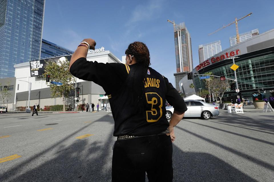 Lakers fan Desiree Engle cheers on announcer Bill Macdonald (crossing street) as he arrives at Staples Center on Thursday.