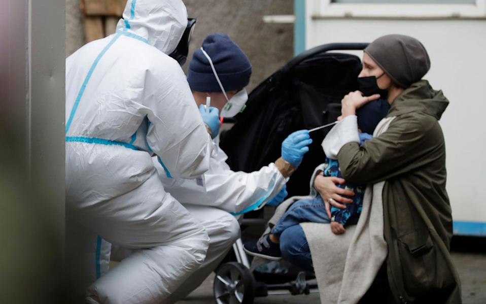 A child is tested at a coronavirus testing site at the Solec Hospital in Warsaw, Poland - AP