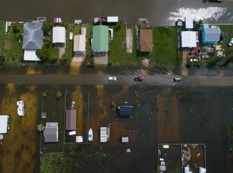 Cars drive on a flooded street in Sargent, Texas, as seen in this aerial photo Wednesday, Sept. 18, 2019. Sargent received 22 inches of rain since tropical storm Imelda hit the area on Tuesday, according to Matagorda County Constable Bill Orton. (Mark Mulligan/Houston Chronicle via AP)