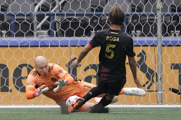 Atlanta United goalkeeper Brad Guzan, left, makes a stop as midfielder Santiago Sosa (5) pulls up from moving in to defend during the first half of an MLS soccer match against the Seattle Sounders, Sunday, May 23, 2021, in Seattle. (AP Photo/Ted S. Warren)