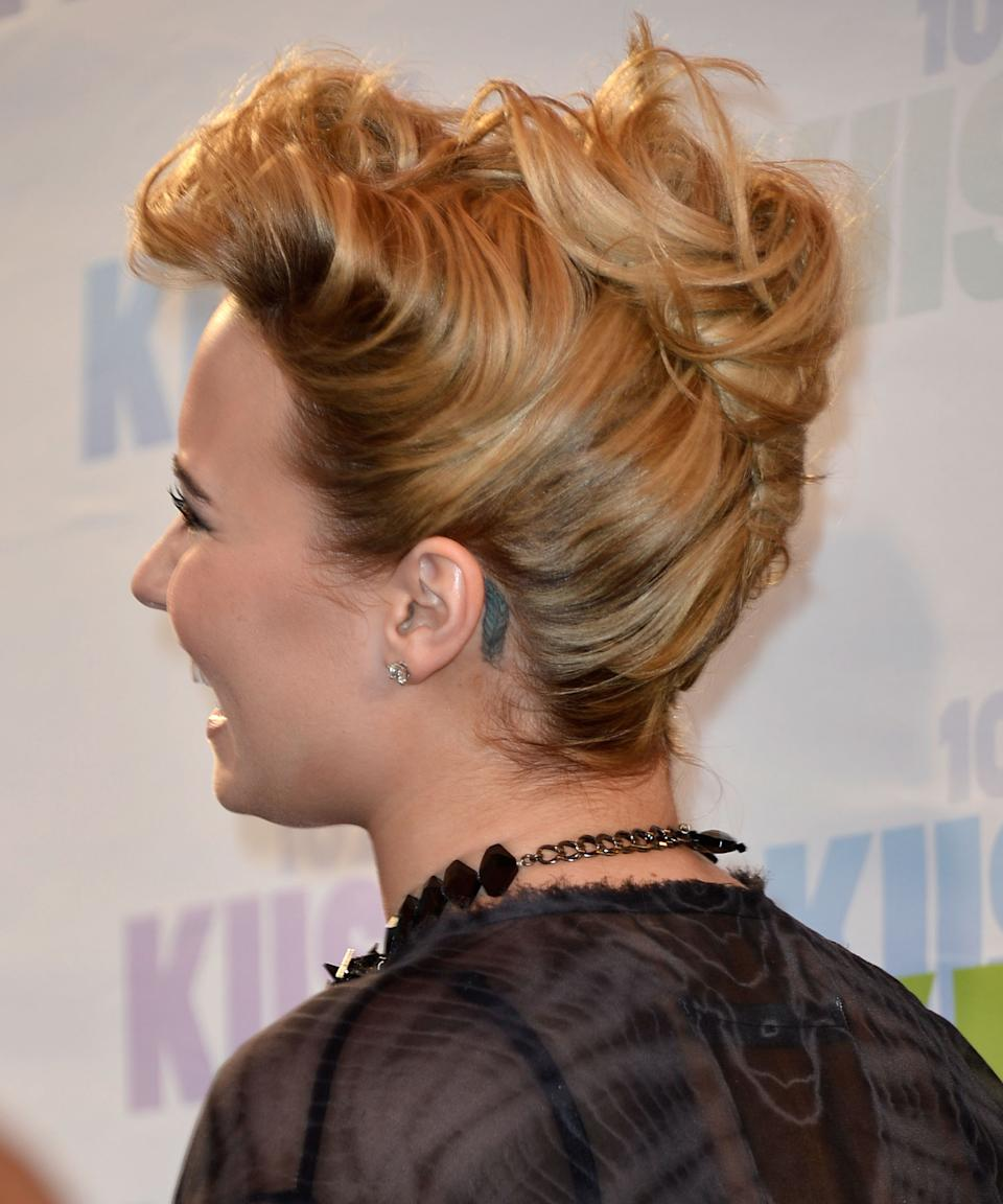 """<h3>Feather</h3><br><br>Lovato added the feather tattoo behind her ear while on a tour bus for the Warped Tour festival back in 2010. She later admitted to <a href=""""https://hollywoodlife.com/2010/09/24/demi-lovato-tattoos-joe-jonas/"""" rel=""""nofollow noopener"""" target=""""_blank"""" data-ylk=""""slk:Hollywood Life"""" class=""""link rapid-noclick-resp"""">Hollywood Life</a> that the design doesn't really mean anything; she just got it because it was cute.<span class=""""copyright"""">Photo: Frazer Harrison/Getty Images.</span>"""
