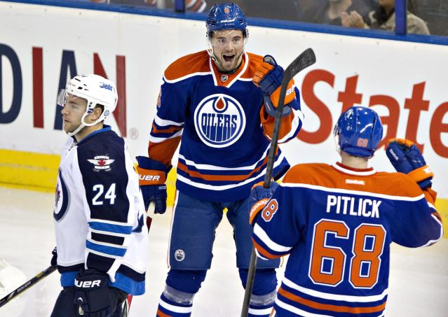 Winnipeg Jets' Grant Clitsome (24) skates by as Edmonton Oilers Jesse Joensuu (6) and Tyler Pitlick (68) celebrate a goal during the second period of an NHL hockey preseason game Monday, Sept. 23, 2013, in Edmonton, Alberta.. (AP Photo/The Canadian Press, Jason Franson)