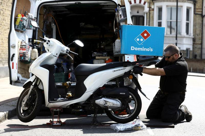 A call out mechanic fixes a Dominos delivery scooter in the Clapham district of London