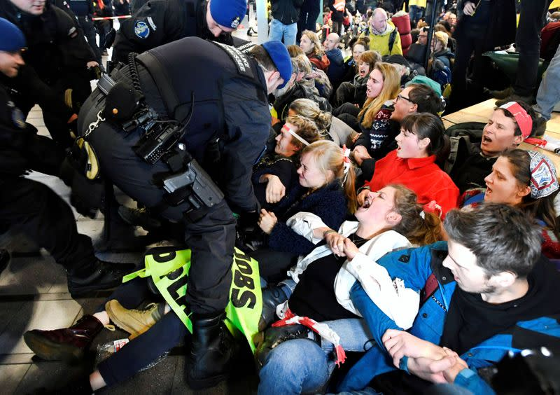Demonstrators react in front of military police as Greenpeace stages a climate protest at Amsterdam Schiphol Airport in Schiphol
