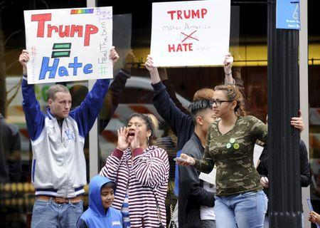 Protesters yell across the street at supporters of U.S. Republican presidential candidate Donald Trump waiting in line for a campaign rally at the downtown Midland Theater in Kansas City, Missouri, March 12, 2016. REUTERS/Dave Kaup