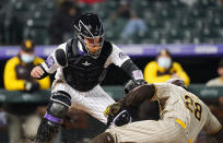 San Diego Padres' Tommy Pham, front, avoids the tag by Colorado Rockies catcher Dom Nunez to score on a ground ball by Ha-Seong Kim during the sixth inning of a baseball game Tuesday, May 11, 2021, in Denver. (AP Photo/David Zalubowski)