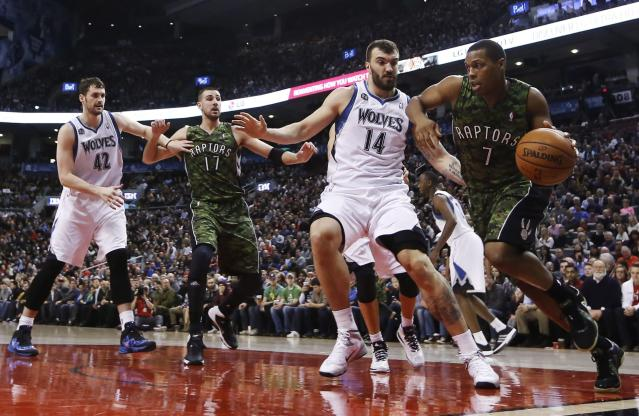 Toronto Raptors' Kyle Lowry, right, drives against Minnesota Timberwolves' Nikola Pekovic (14) and Kevin Love (42) during the first half of an NBA basketball game Friday, Jan. 17, 2014, in Toronto. Second from left is Toronto's Jonas Valanciunas. (AP Photo/The Canadian Press, Mark Blinch)