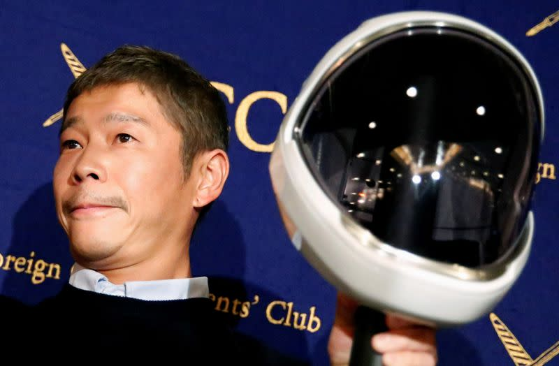 FILE PHOTO: Japanese billionaire Maezawa, founder and chief executive of online fashion retailer Zozo, who has been chosen as the first private passenger by SpaceX, poses for photos as he attends a news conference in Tokyo