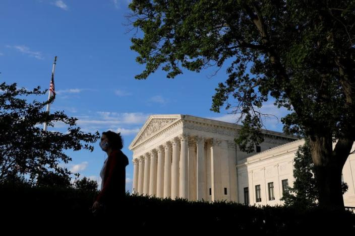 FILE PHOTO: A person in a mask walks past the United States Supreme Court Building in Washington, D.C.