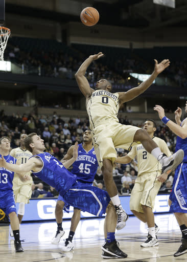 Wake Forest's Codi Miller-McIntyre (0) shoots after running into UNC Asheville's Alec Wnuk (2) during the first half of an NCAA college basketball game in Winston-Salem, N.C., Friday, Nov. 14, 2014. Miller-McIntyre was called for a foul on the play. (AP Photo/Chuck Burton)