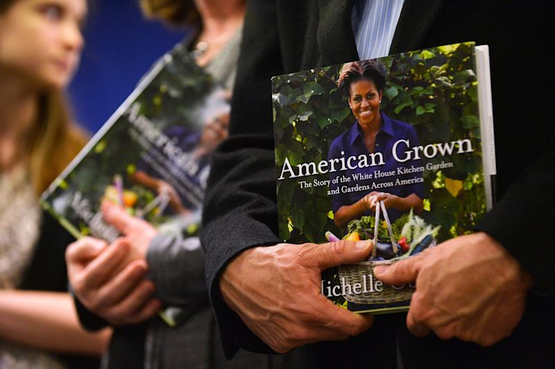 People wait in a line with their copies of US First Lady Michelle Obama's book 'American Grown: The Story of the White House Kitchen Garden and Gardens Across America,' to get them autographed at Politics & Prose in Washington, DC, on May 7, 2013. Photo credit: JEWEL SAMAD/AFP/Getty Images