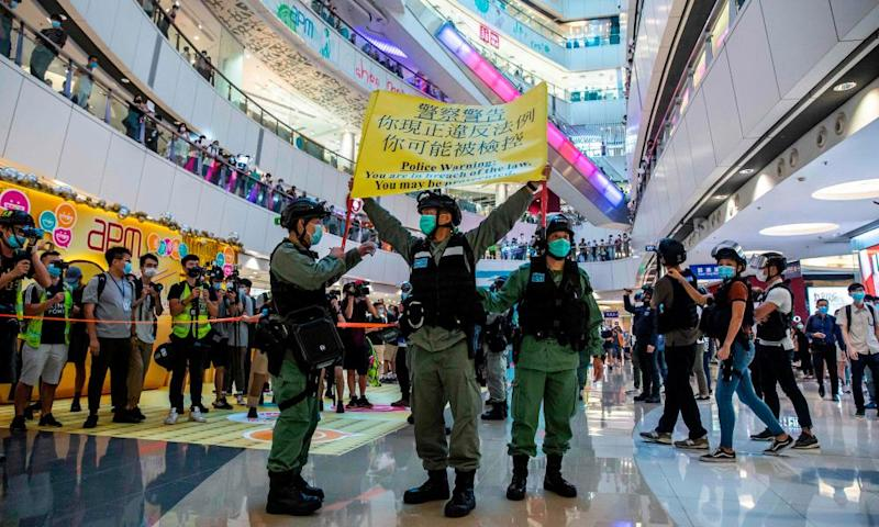 Police hold up a warning flag during a pro-democracy demonstration at a mall in Hong Kong on Monday.