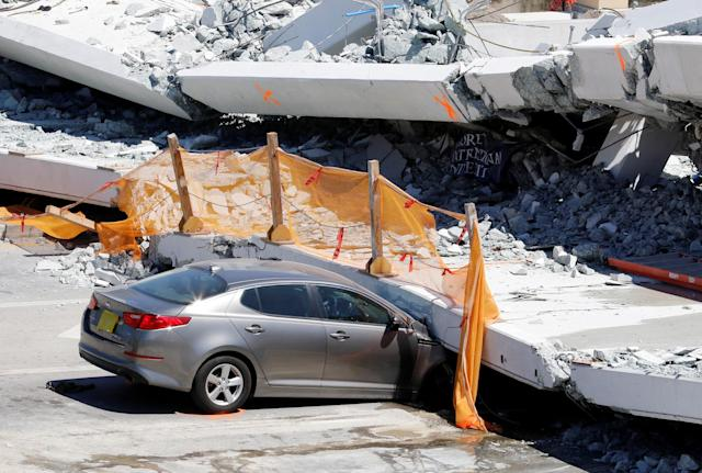 A damaged car is seen partially trapped as workers remove debris from a collapsed pedestrian bridge at Florida International University in Miami, Florida, U.S., March 16, 2018. REUTERS/Joe Skipper TPX IMAGES OF THE DAY