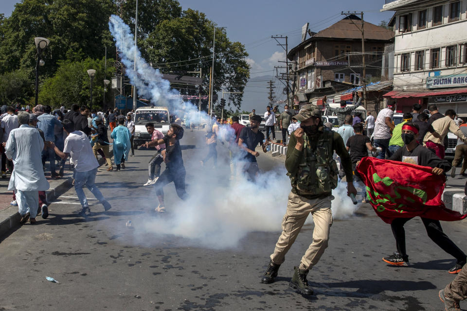 A Kashmiri Shiite Muslim throws back tear gas shell fired by Indian police during a religious procession in central Srinagar, Indian controlled Kashmir, Tuesday, Aug. 17, 2021. Police in Indian-controlled Kashmir on Tuesday fired tear gas and warning shots to disperse hundreds of Shiite Muslims, while detaining dozens who attempted to participate in processions marking the Muslim month of Muharram. (AP Photo/Dar Yasin)