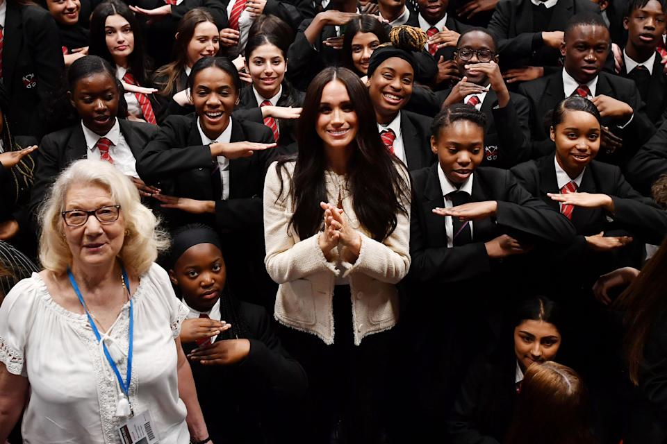 LONDON, ENGLAND - MARCH 06: (EDITOR'S NOTE: Alternative crop of image #1205706931) Meghan, Duchess of Sussex poses with school children making the 'Equality' sign following a school assembly during a visit to Robert Clack School in Dagenham to attend a special assembly ahead of International Women's Day (IWD) held on Sunday 8th March, on March 6, 2020 in London, England.   (Photo by Ben Stansall-WPA Pool/Getty Images)