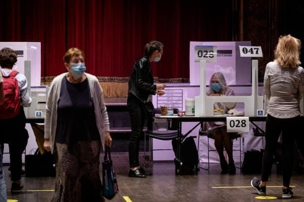 Voters at a University-Rosedale polling station on Monday. Some people reported it had been a busy, and at times frustrating day for voters in the city.  (Evan Mitsui/CBC - image credit)