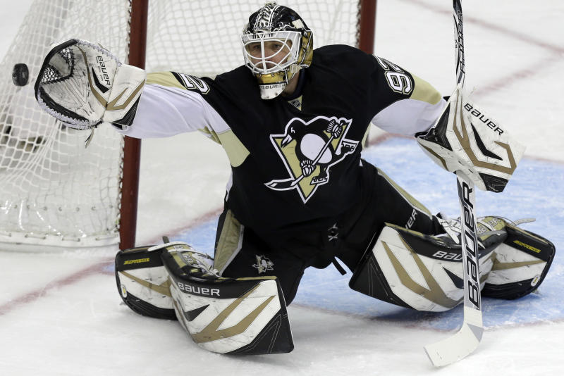 Pittsburgh Penguins goalie Tomas Vokoun (92) reaches for a shot in the first period of an NHL hockey game against the Winnipeg Jets in Pittsburgh, Thursday, March 28, 2013. (AP Photo/Gene J. Puskar)