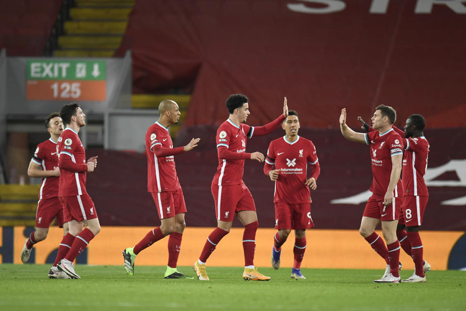 Liverpool\s team players celebrate after Leicester's Jonny Evans scored an own goal during the English Premier League soccer match between Liverpool and Leicester City at Anfield stadium in Liverpool, England, Sunday, Nov. 22, 2020. (Peter Powell/Pool via AP)