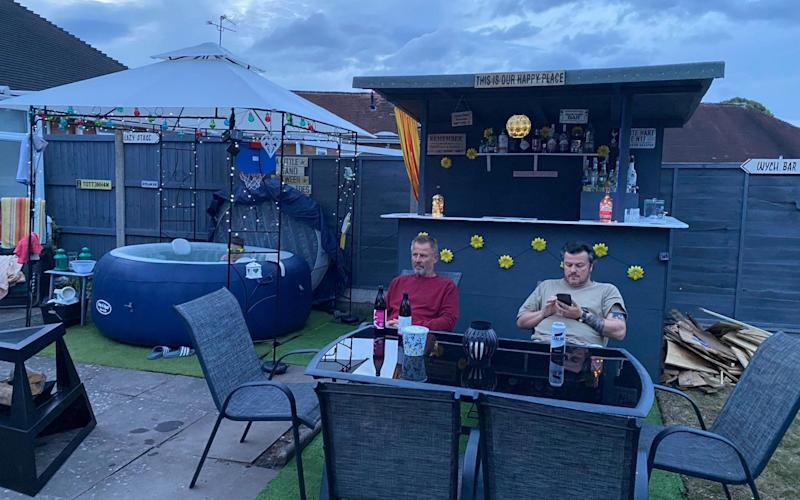 Two men sit at table at back garden Glastonbury - Fiona Rees/PA