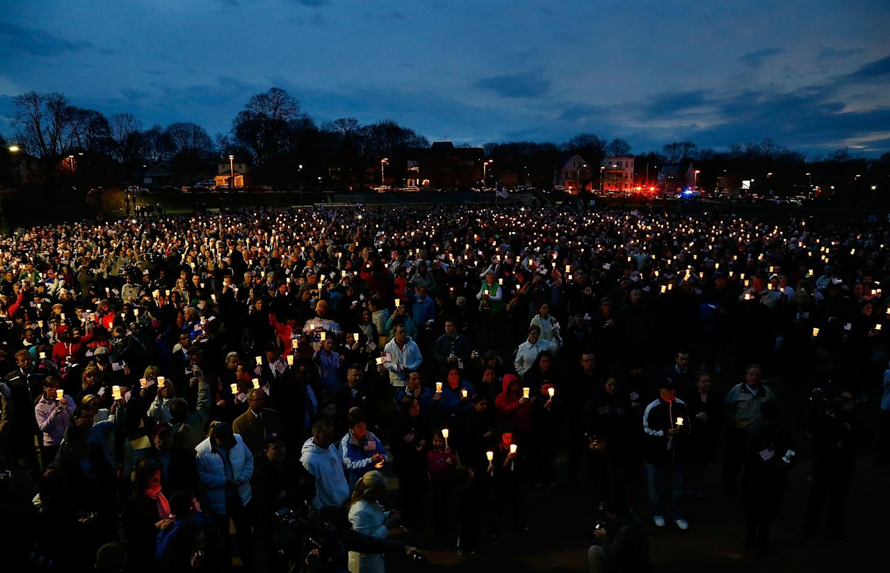 BOSTON, MA - APRIL 16: People gather with candles during a vigil for eight-year-old Martin Richard, from Dorchester, who was killed by an explosion near the finish line of the Boston Marathon on April 16, 2013 at Garvey Park in Boston, Massachusetts. The twin bombings resulted in the deaths of three people and hospitalized at least 128. The bombings at the 116-year-old Boston race resulted in heightened security across the nation with cancellations of many professional sporting events as authorities search for a motive to the violence. (Photo by Jared Wickerham/Getty Images)