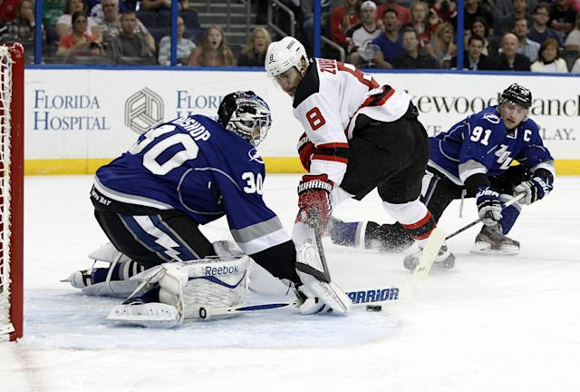 Tampa Bay Lightning center Steven Stamkos (91) comes in to help goalie Ben Bishop (30) defend on a shot by New Jersey Devils right wing Dainius Zubrus (8), of Lithuania, during the first period of an NHL hockey game Saturday, March 15, 2014, in Tampa, Fla. (AP Photo/Brian Blanco)