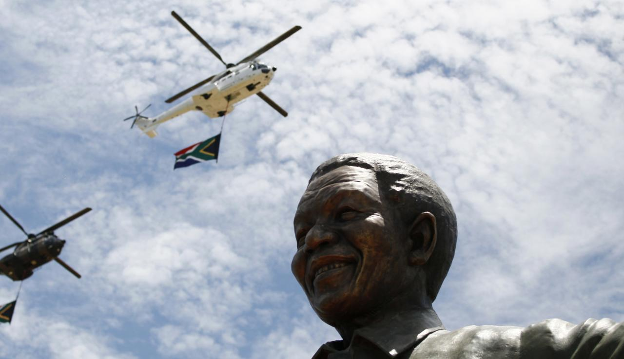 South African military and police helicopters fly past a 9-metre (30-feet) bronze statue of the late former President Nelson Mandela after it was unveiled as part of the Day of Reconciliation Celebrations at the Union Buildings in Pretoria December 16, 2013. The day also marks the commemoration of the centenary of the Union Buildings, one of the most iconic structures in South Africa. The unveiling of the statue is intended as acknowledgement of the contribution of the first president of a democratic South Africa, a symbol of national reconciliation and unity. REUTERS/Thomas Mukoya (SOUTH AFRICA - Tags: OBITUARY POLITICS TRAVEL ANNIVERSARY)