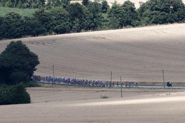 The pack passes wheat fields during the fifth stage of the Tour de France cycling race over 204.5 kilometers (127 miles) with start in Lorient and finish in Quimper, France, Wednesday, July 11, 2018. (AP Photo/Christophe Ena)