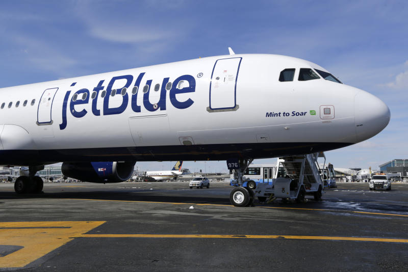 FILE- In this March 16, 2017, file photo, a Jet Blue airplane at John F. Kennedy International Airport in New York. A new report says U.S. airlines are increasing their emissions of climate-changing gases much faster than they are boosting fuel efficiency. The International Council on Clean Transportation said Thursday, Sept. 12, 2019 that carbon dioxide emissions and fuel burning rose 7% from 2016 to 2018, overshadowing a 3% gain in fuel efficiency. The report ranked Frontier Airlines the most efficient among the 11 largest U.S. airlines. JetBlue ranked last. (AP Photo/Seth Wenig, File)
