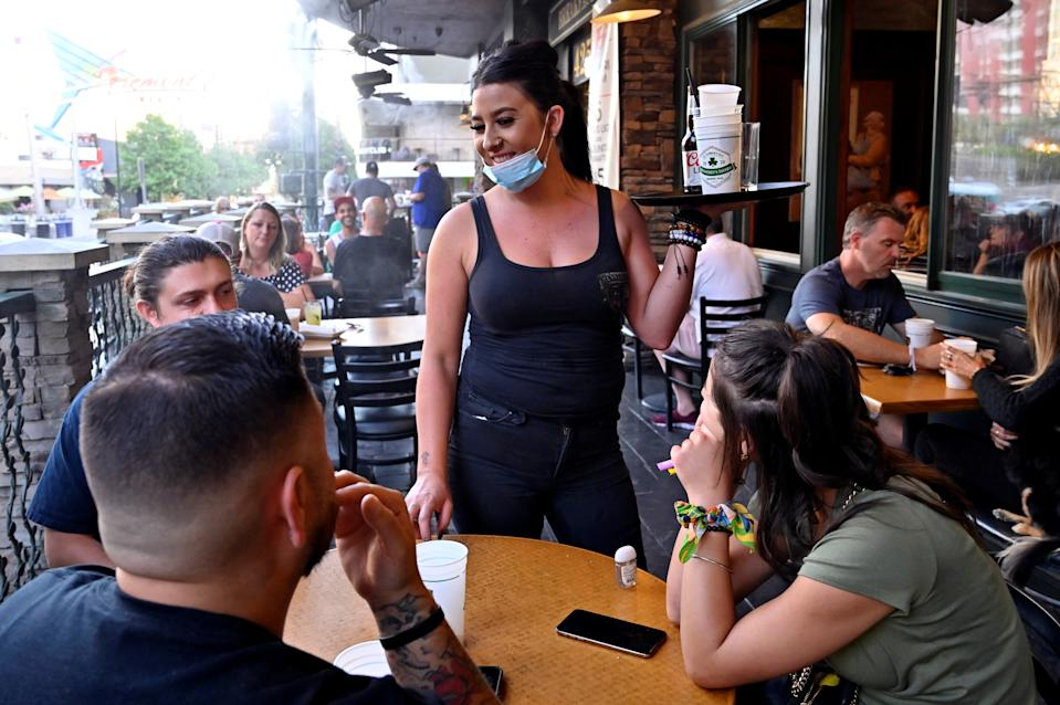 Server Timi Sanchez waits on customers at Hennessey's Tavern as restaurants are opening for business on sidewalks as restrictions to prevent the spread of coronavirus disease (COVID-19) are eased in Las Vegas, Nevada, U.S., May 15, 2020.  REUTERS/David Becker