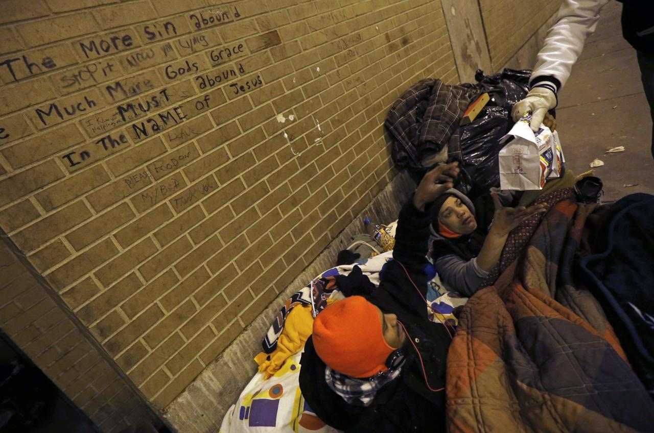 Doctor Patrick Angelo hands out food to homeless people under the overpasses on Lower Wacker Drive in Chicago, Illinois, January 7, 2014. Angelo visits the homeless several times a week to hand out food, clothing and blankets to those living on the streets with funding coming from his oral surgery medical practice and profits from his healthcare company. Angelo is in his 13th year doing charity work. Picture taken January 7, 2014. REUTERS/Jim Young (UNITED STATES - Tags: SOCIETY POVERTY)