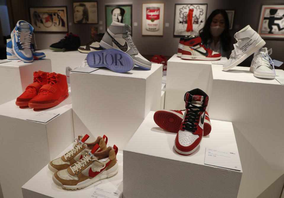 A selection of sneakers to be sold as part of the Pop Culture auction at Bonhams auction house in London, Thursday, Oct. 1, 2020. Including, a pair of Nike Sky Jordan 1, 1985 with Chicago Bulls White, Black and Red colour way estimated at 14,000-16,000 UK pounds, bottom right, a pair of Dior X Nike Air Jordan 1 High OG sneakers 10,000-12,000 UK pounds (US dollars 13-15,000), top centre, and a pair of Nike Air Yeezy 2 Red October 2014, 12,000-14,000 UK pounds ( US dollars 15-18,000), when sold in the auction on Oct. 8. (AP Photo/Alastair Grant)