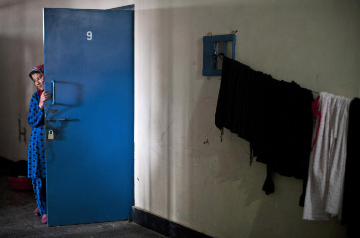 """Picture taken March 28, 2013 shows an Afghan female prisoner outside her cell at Badam Bagh, Afghanistan's central women's prison, in Kabul, Afghanistan. Twohundred-and-two women living in the six- year- old jail, the majority of the women are serving sentences of up to seven years for leaving their husbands, refusing to accept a marriage arranged by their parents, or choosing to leave their parent's home with a man of their choice, all so-called """"moral"""" crimes(. AP Photo/Anja Niedringhaus)"""