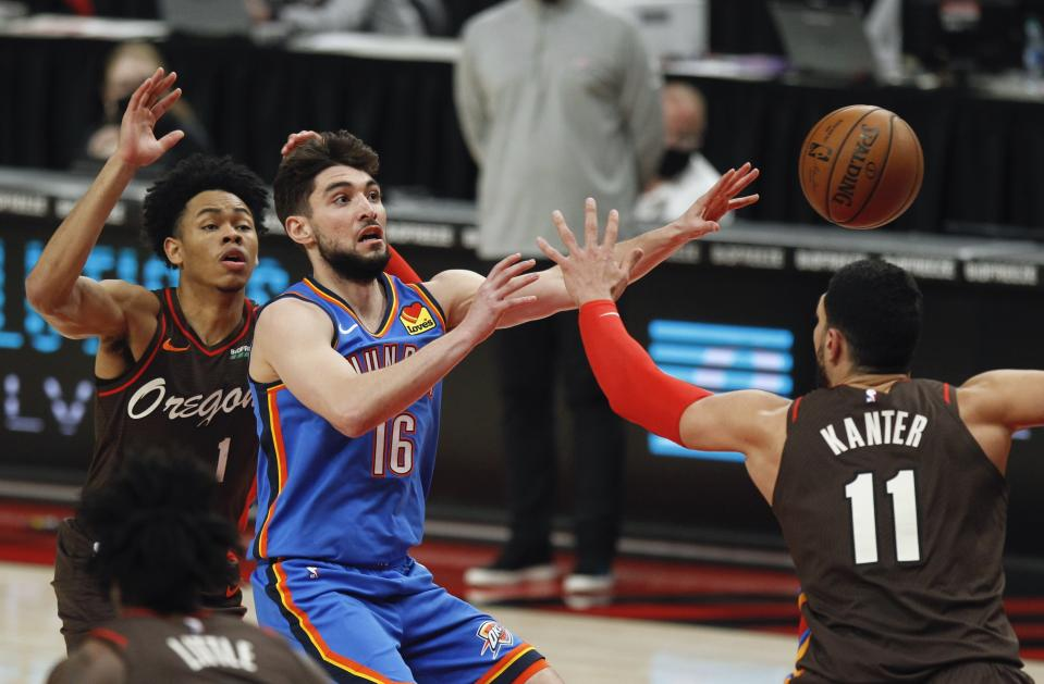 Oklahoma City Thunder guard Ty Jerome, center, passes as Portland Trail Blazers guard Anfernee Simons, left, and center Enes Kanter, right, defend during the first half of an NBA basketball game in Portland, Ore., Saturday, April 3, 2021. (AP Photo/Steve Dipaola)