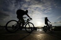 People wearing face masks to help curb the spread of the coronavirus are silhouetted as they ride bicycles near the Han River in Seoul, South Korea, Thursday, Sept. 23, 2021. (AP Photo/Lee Jin-man)