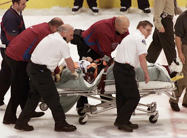 FILE - In this March 8, 2004, file photo, Colorado Avalanche NHL hockey player Steve Moore is taken off the ice by medical staff after he was hit by Vancouver Canucks' Todd Bertuzzi during the third period of NHL action in Vancouver, British Columbia. A settlement has been reached in Moore's lawsuit against Bertuzzi for his career-ending hit during an NHL game 10 years ago. (AP Photo/Chuck Stoody, File)