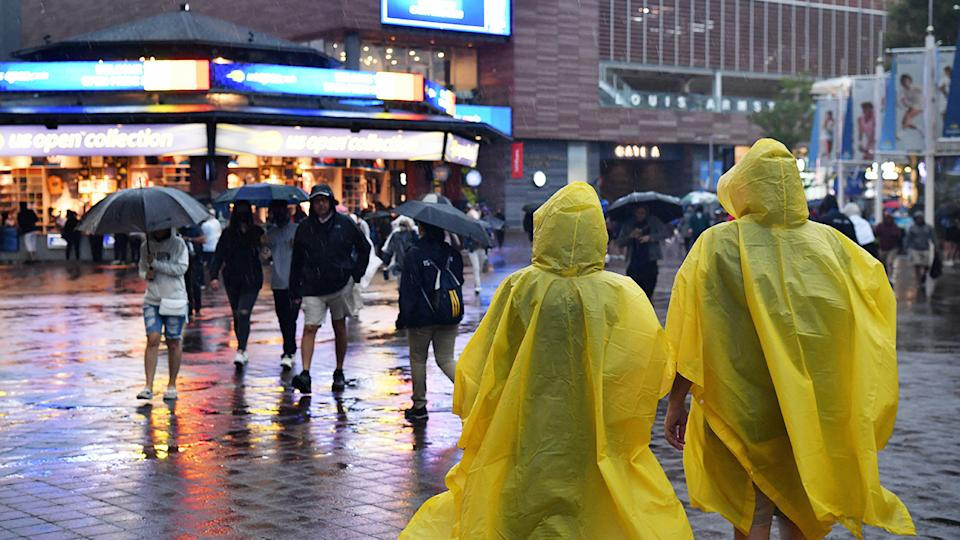 People wearing ponchos, pictured here walking under heavy rain at the US Open.