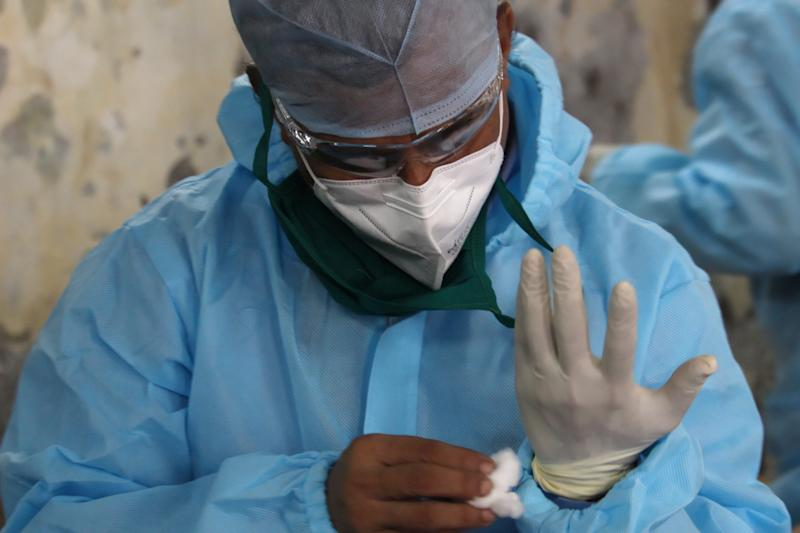 A healthcare worker wearing personal protective equipment (PPE) uses a cotton ball to clean his gloves during a screening for plasma blood donation in Mumbai, India on July 25, 2020. India has become the third country after the United States and Brazil, to cross 01 million COVID-19 cases. (Photo by Himanshu Bhatt/NurPhoto via Getty Images)