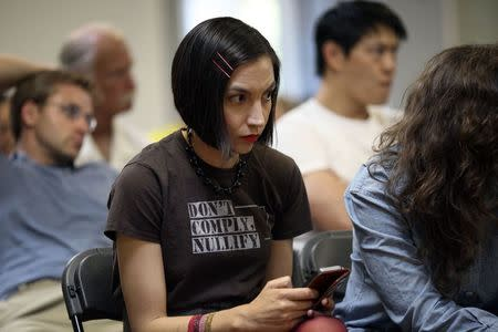 """Melinda McCrady texts and watches a speaker while wearing a shirt bearing the Tenth Amendment Center motto, """"Don't comply. Nullify"""", referring to a movement to make certain laws ineffectual through the tactics of nullification laws or widespread non-compliance, at a meeting of so-called """"Liberty Kids"""" libertarian Republican activists in Burbank, California, July 27, 2014. REUTERS/David McNew"""