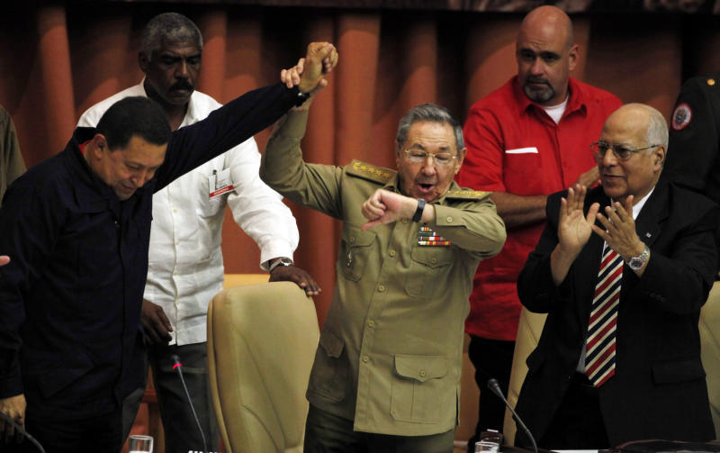 Cuba's President Raul Castro, center, raises the arm of Venezuela's President Hugo Chavez while checking his watch as Cuba's Vice-President Ricardo Cabrisas applauds at the end of a meeting in Havana, Cuba, Monday Nov. 8, 2010. Castro announced that Cuba will hold a long-delayed, and much-anticipated, Communist Party Congress next April and leaders will use the meeting to chart a new economic future for the island while Venezuela's socialist leader vowed to continue supporting the Cuban revolution both economically and politically. (AP Photo/Javier Galeano)