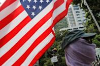 A student protester holds a U.S. flag near the Goddess of Democracy statue before the start of a student march on the campus of the Chinese University of Hong Kong