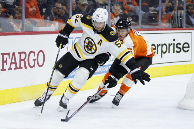 Philadelphia Flyers' Philippe Myers, right, knocks the puck away from Boston Bruins' Sean Kuraly during the third period of a preseason NHL hockey game Thursday, Sept. 19, 2019, in Philadelphia. Boston won 3-1. (AP Photo/Matt Slocum)