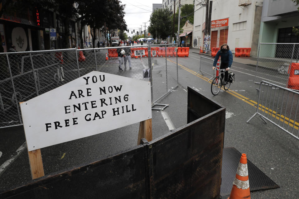 """A cyclist rides near a sign that reads """"You are now entering free Cap Hill,"""" Thursday, June 11, 2020, inside what is being called the """"Capitol Hill Autonomous Zone"""" in Seattle. Following days of violent confrontations with protesters, police in Seattle have largely withdrawn from the neighborhood, and protesters have created a festival-like scene that has President Donald Trump fuming. (AP Photo/Ted S. Warren)"""